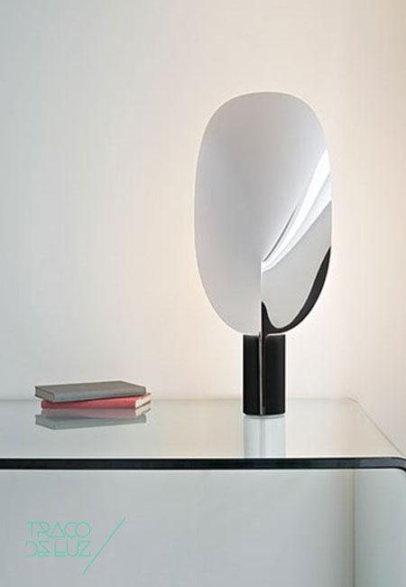 """Serena é um candeeiro de mesa com design de Patricia Urquiola para a FLOS. Inspirado no mundo natural, recordando um elemento floral, Serena é composto por uma base cilíndrica ao qual se fixa uma """"folha"""", de posição ajustável, que filtra a luz emitida. Inclui controlador de intensidade de luz. Dimensões ø 7,8 cm base x 63,4 cm altura Cor preto / niquel Fonte de Luz LED incluído Prazo de entrega 2 a 3 semanas + info Para + info sobre quantidades, cores e tamanhos eshop@tracoluz.com"""